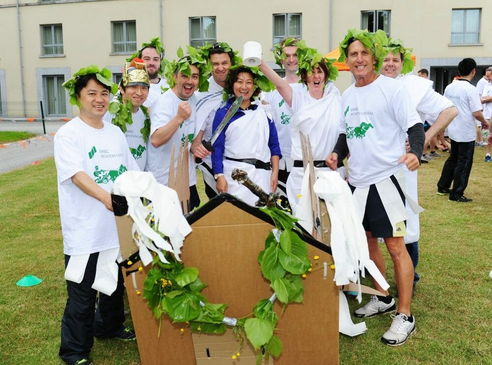 Delegates dressed in roman clothing standing next to the cardboard chariot they built during their corporate away day.