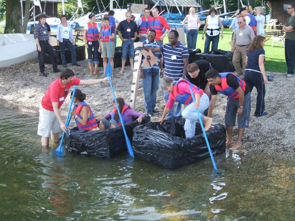 Delegates getting into & standing beside a cardboard boat they built during their team-building activity with Orangeworks.