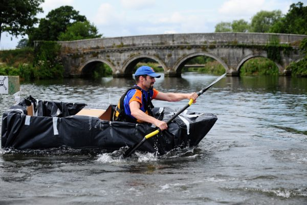 Delegate rowing down the river in a cardboard boat he built during his team-building activity with Orangeworks.