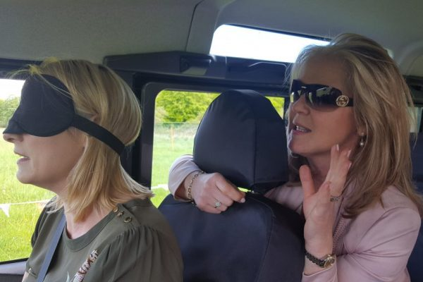 Blindfolded delegate driving a defender around off-road tracks while her colleague guides her on where to drive.