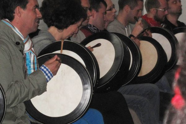 Delegates learning to play the bodhran during the Orangeworks irish themed activity.