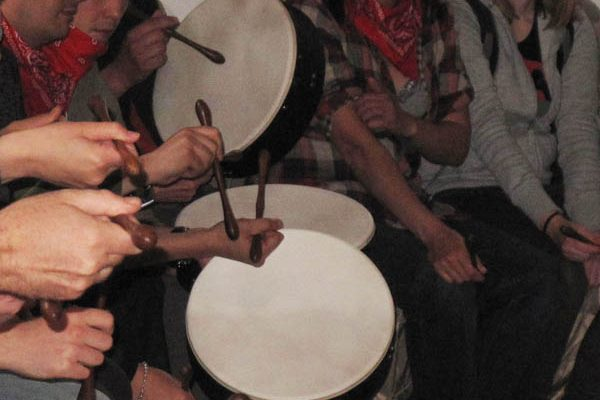 People holding bodhran beaters as they play and enjoy the team activity by Orangeworks.