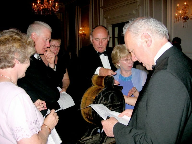 Delegates deliberating over an antique during The Curio Show, a corporate evening interaction, hosted by Orangeworks.