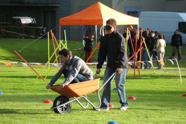 Blindfolded delegate pushing his colleague in a wheelbarrow during their corporate sports day activity with Orangeworks.