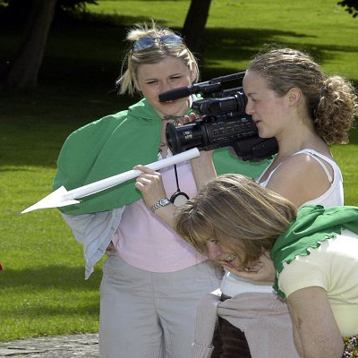 Girl using a camera filming her teammates as they recreate a hollywood movie during Fifteen Famous Minutes by Orangeworks.