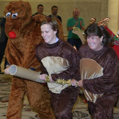 two people pulling a sleigh with rudolf the Reindeer running along beside them during Orangeworks team Christmas activity.