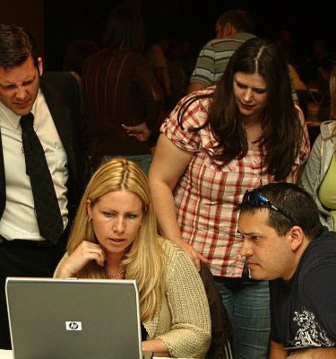 Delegates looking at a laptop while discusses their final edits during the team building activity Making the News.