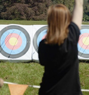 The back of delegate cheering after hitting the archery target during her outdoor team building activity with Orangeworks.