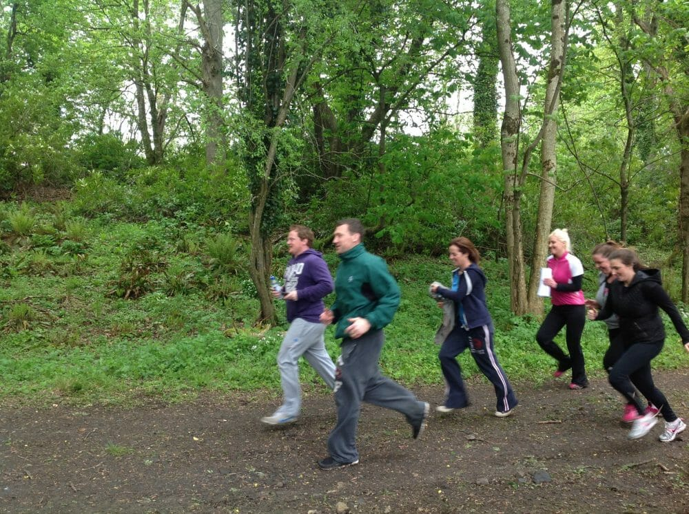 A team running through the forest during Best of British, an outdoor team building activity by Orangeworks.
