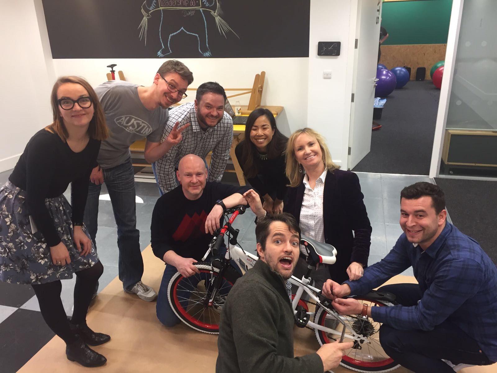 Teams smile for a photo while in the middle of putting their bike together during Orangeworks' Charity Bike Build.
