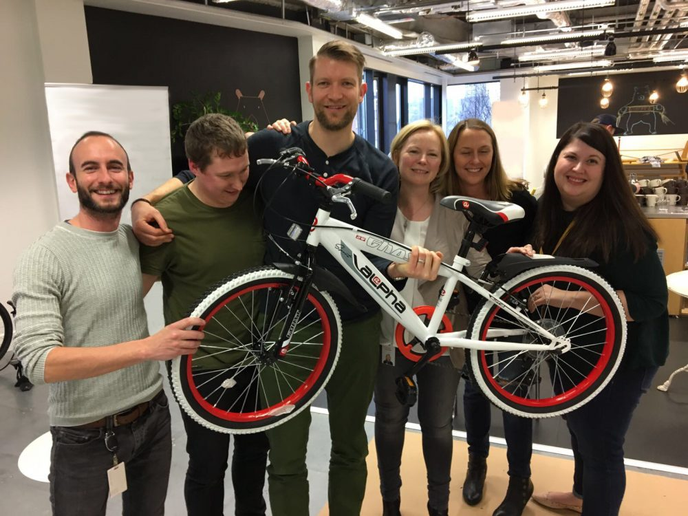 Team smiling with their newly built bike during Charity Bike Build, a charity themed corporate event.
