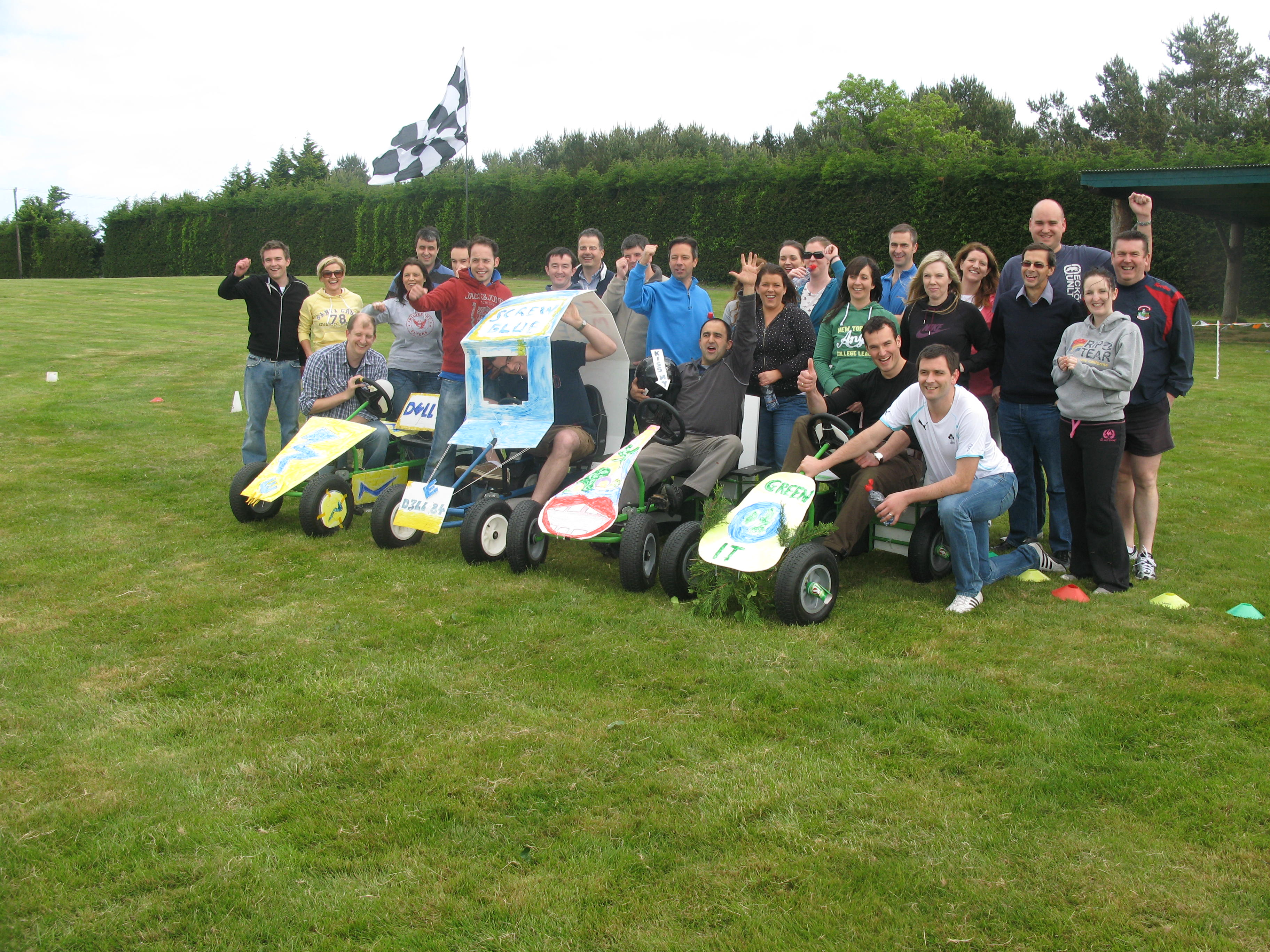 A group of delegates smile next to their newly constructed go karts