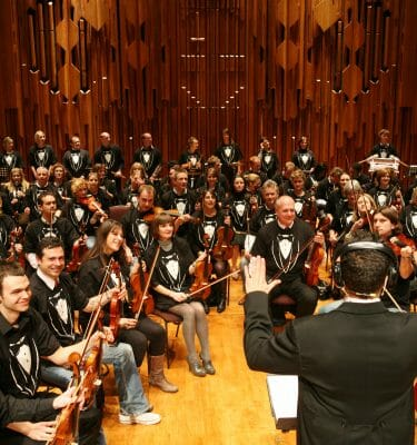 Orchestrate conductor and delegates getting ready to perform the finale of the orchestra they created together.