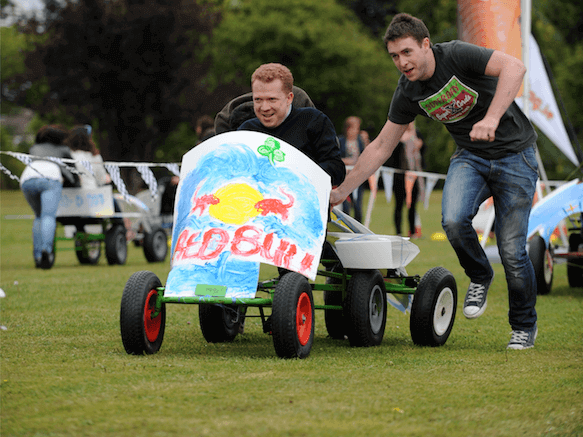 One delegate pushes another in their Go Kart during Thunder Races powered by Orangeworks.