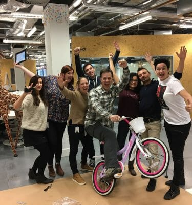 Delegates smile for a photo with the bike they have built for charity during Orangeworks team charity event Build a Bike.