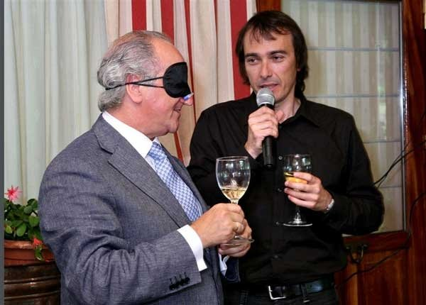 Blindfolded man tasting his wine in Calling the Shots, a corporate evening interaction hosted by Orangeworks.