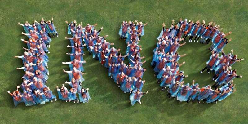 Employees of the company INO standing in the shape of their logo, using their bodies as pixels during Orangeworks team bonding activity.