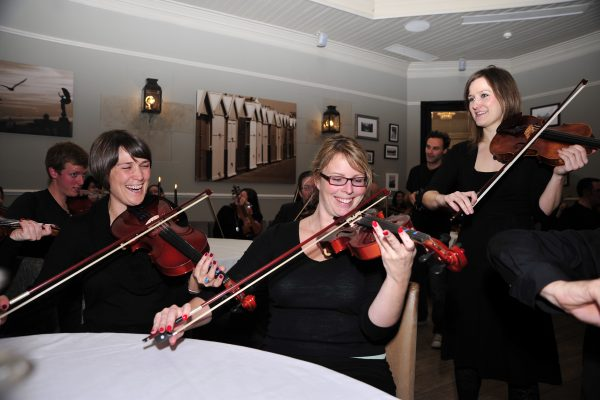 3 delegates smiling and laughing while learning how to play the violin, as part of their staff away day with Orangeworks.