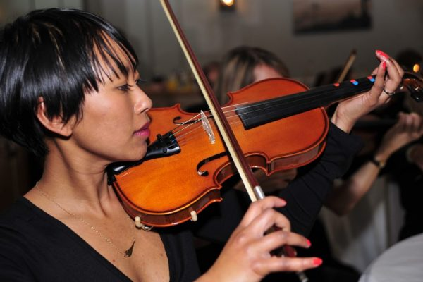 Delegate learning how to play the violin during a music-themed team building activity, Crescendo, with Orangeworks.