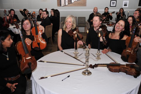 The team hold their violins whilst smiling