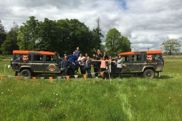 Delegates standing beside the Bear Grylls Survival Academy vehicles.
