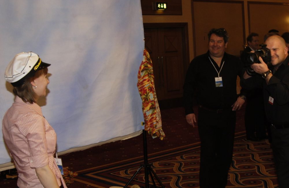 A delegate of the corporate icebreaker event, In The Picture, wearing a sailor hat and smiling for a photo taken by a photographer.