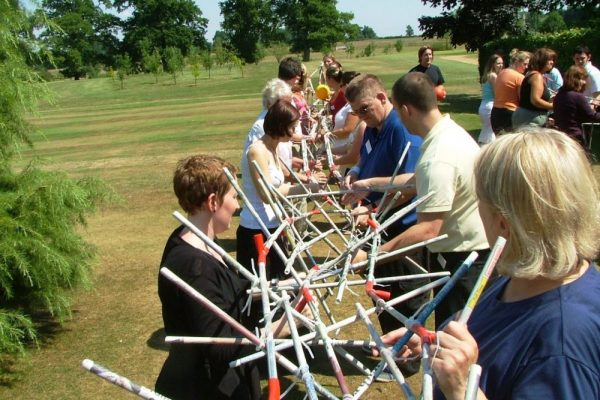 Delegates working together to build the final construction of the team building game, Mexican Railway.