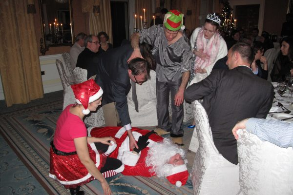 Participants gathered around a murdered Santa, trying to figure out the murder mystery game hosted by Orangeworks.