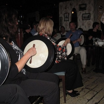 A group of people holding bodhrans, learning how to play them during Orangeworks team building bodhran workshop.