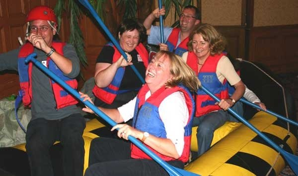 Delegates wearing lifejackets, holding ores and sitting in a boat as they take part in River Runner, a team-building game.
