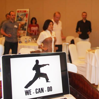 The We Can Do app open on an iPad while delegates practice their karate poses in the background and are enjoying the corporate wellness activity.