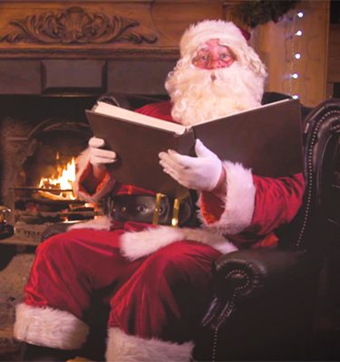 Santa Claus sitting next to the fire with a book