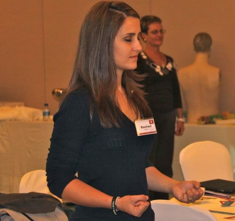 A participant of We Can Do, an employee wellness activity by Orangeworks, with her eyes closed holding a karate pose.