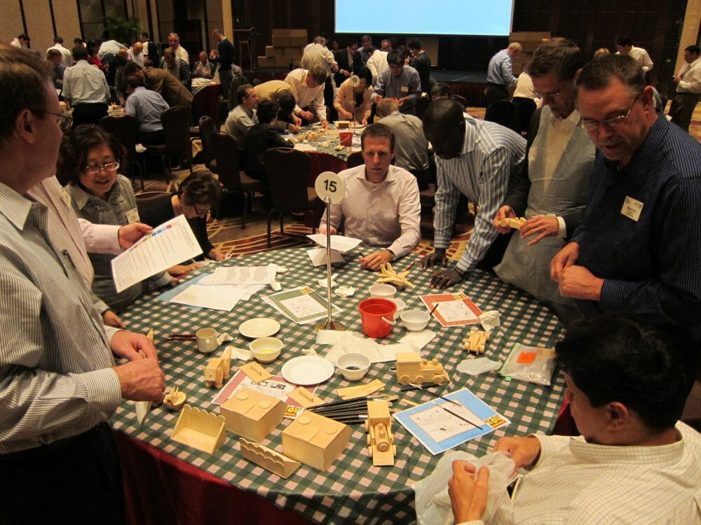 Teams working together around a table building wooden toys during an Orangeworks team building event called toy factory.