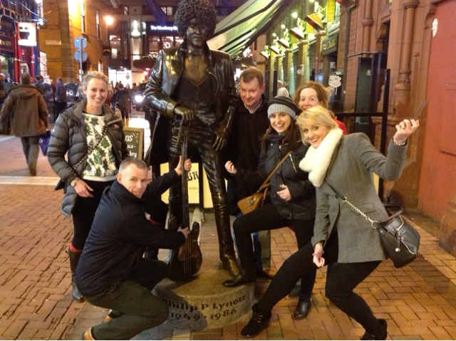 Teams standing around a statue of Luke Kelly doing the photo challenge of Go Team Hunt for Santa with Orangeworks.