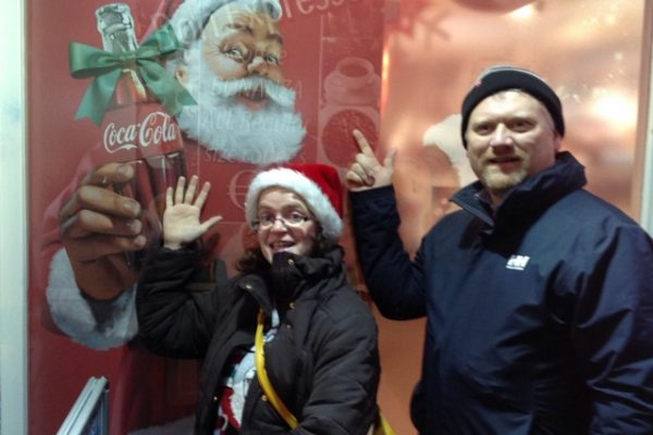 Teams pose with a Coca Cola advertisement during Santa Claus Treasure Hunt