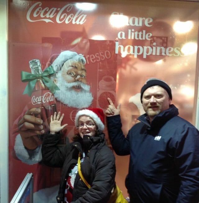 Teams pose with a Coca Cola advertisement during Orangeworks Go Team Christmas Treasure Hunt.