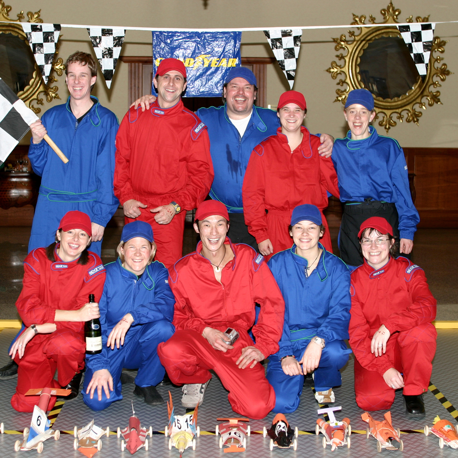 Teams wearing red and blue overalls posing with their model cars ready for the final race of Orangeworks activity Team Torque