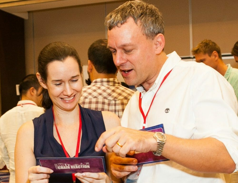 Two delegates reading the cue cards of the Orangeworks team building activity called Chain Reaction table top.