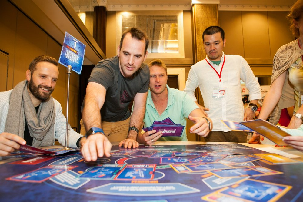 Delegates playing a board game style team-building event called chain reaction table top with Orangeworks.