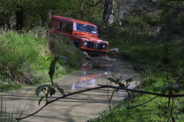 Orangeworks landrover driving through muddy tracks of an offroad driving track.