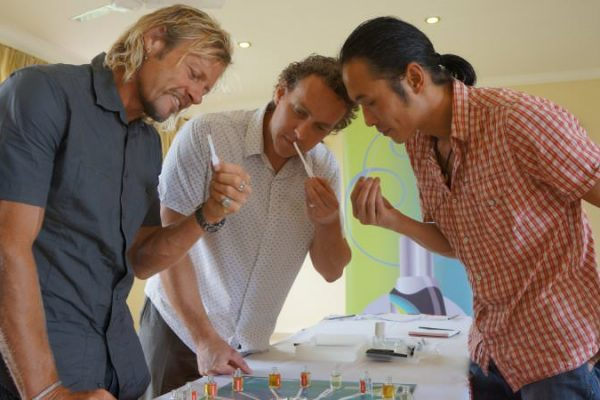 3 men smelling their fragrance strips deciding what fragrance to make during their team building event with Orangeworks.
