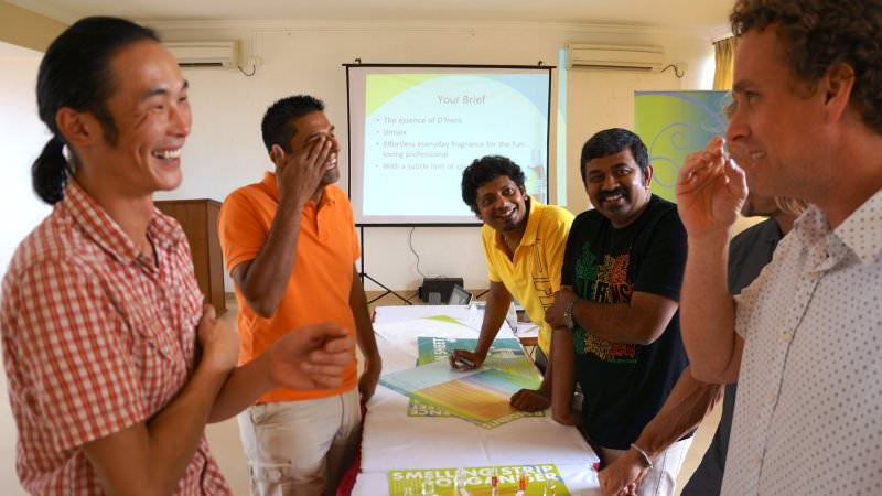 Participants of the perfume making team building activity laughing and chatting about what they are creating.