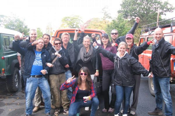 Delegates standing together cheering and smiling as they completed their Orangeworks outdoor team building activity.