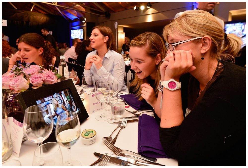 Delegates laugh as they watch what's on their iPads during their corporate evening interaction with Orangeworks.