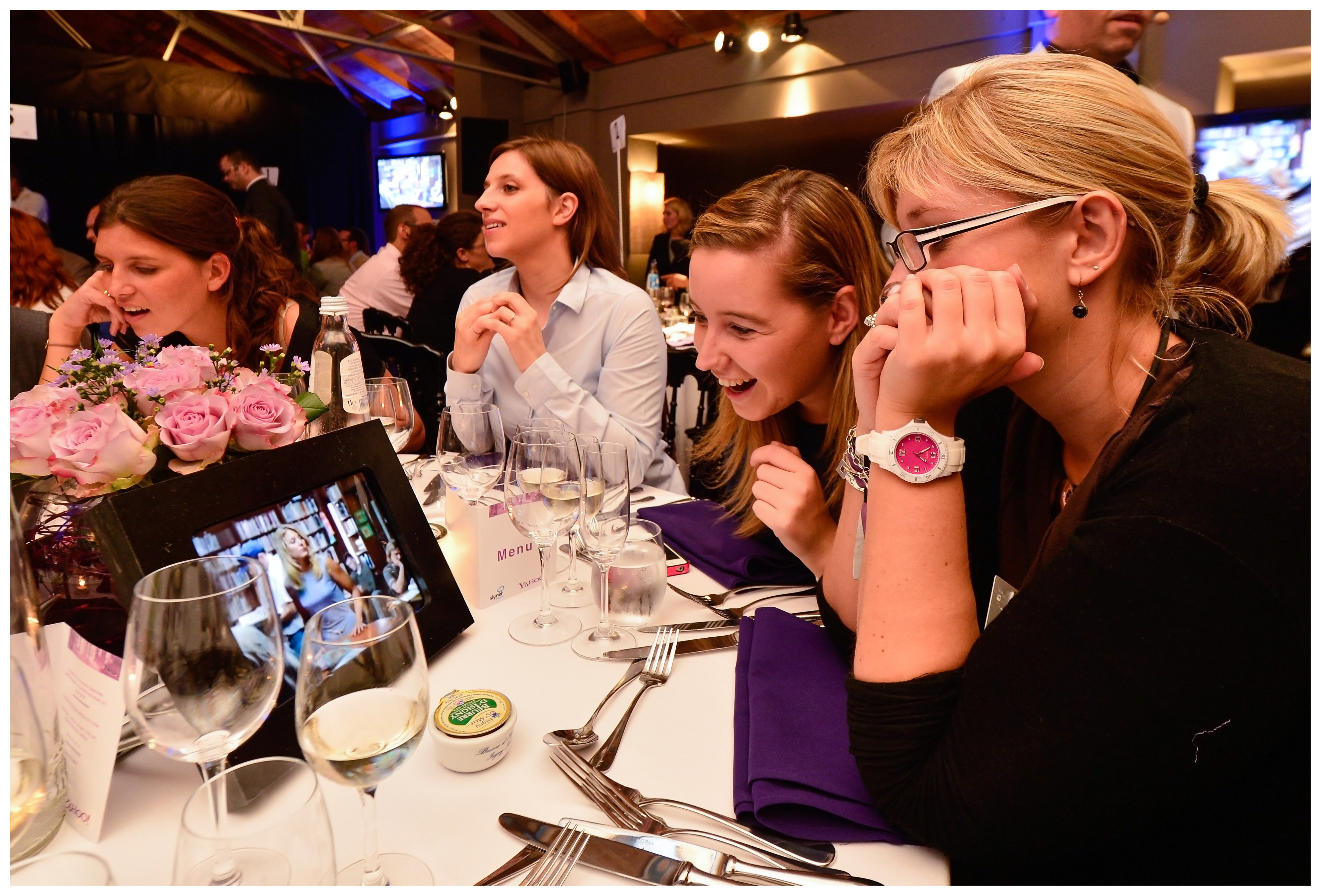 Delegates laugh as they watch what's on their iPads