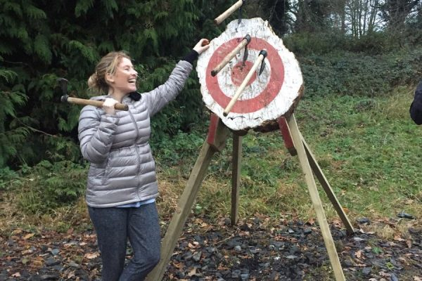 Happy delegate smiling next to her axe throwing target
