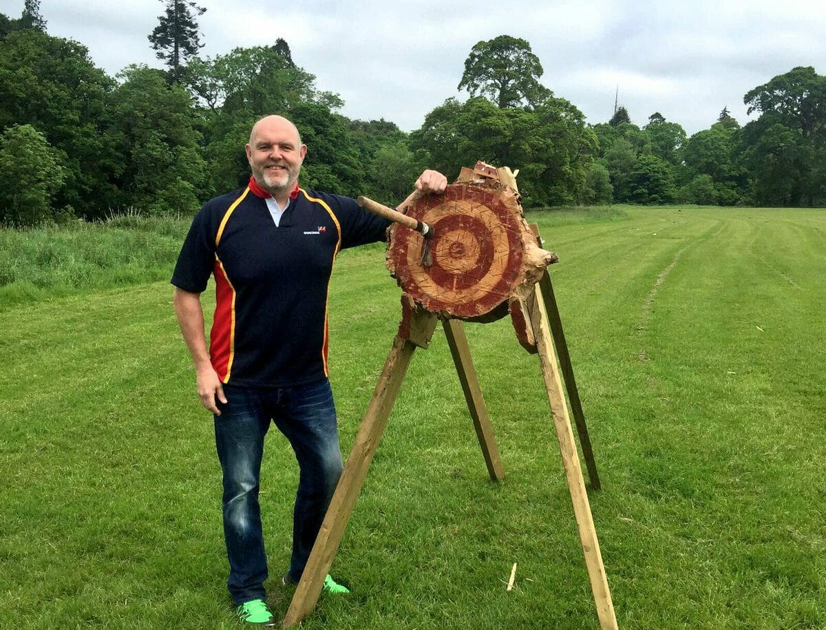 Smiling delegate next to axe throwing target