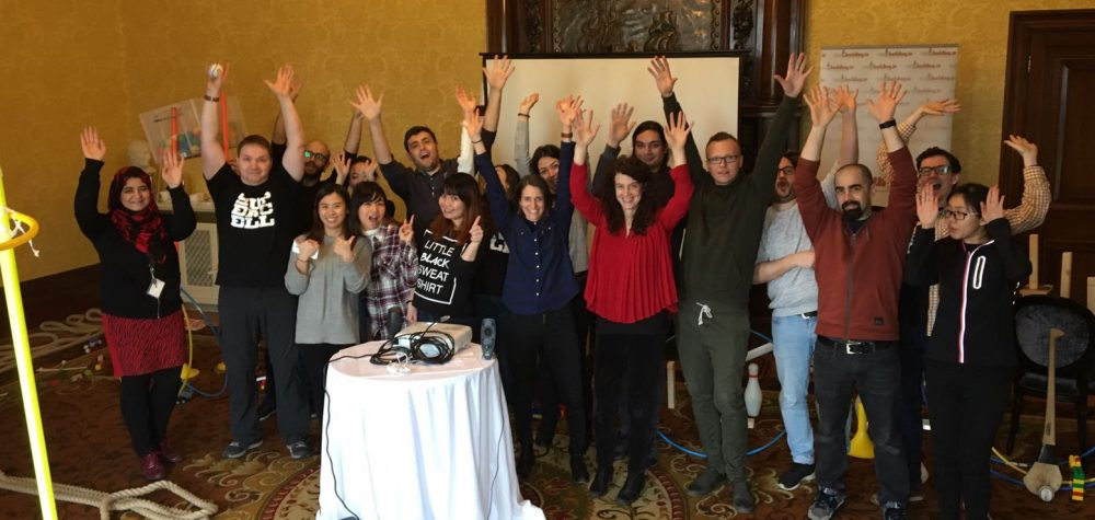 Delegates standing with their hands in the air during their innovative team building activity, Chain Reaction Lifesize.