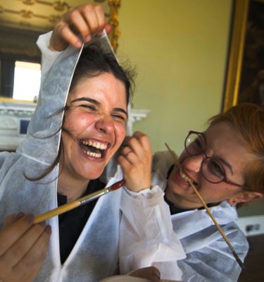 Delegates laughing together with paint brushes in hand